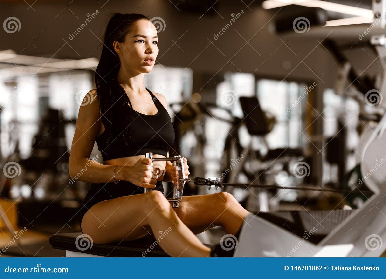 Het jonge slanke donker-haired meisje gekleed in zwarte sportenbovenkant en borrels werkt op de oefeningsmachine uit in de gymnas