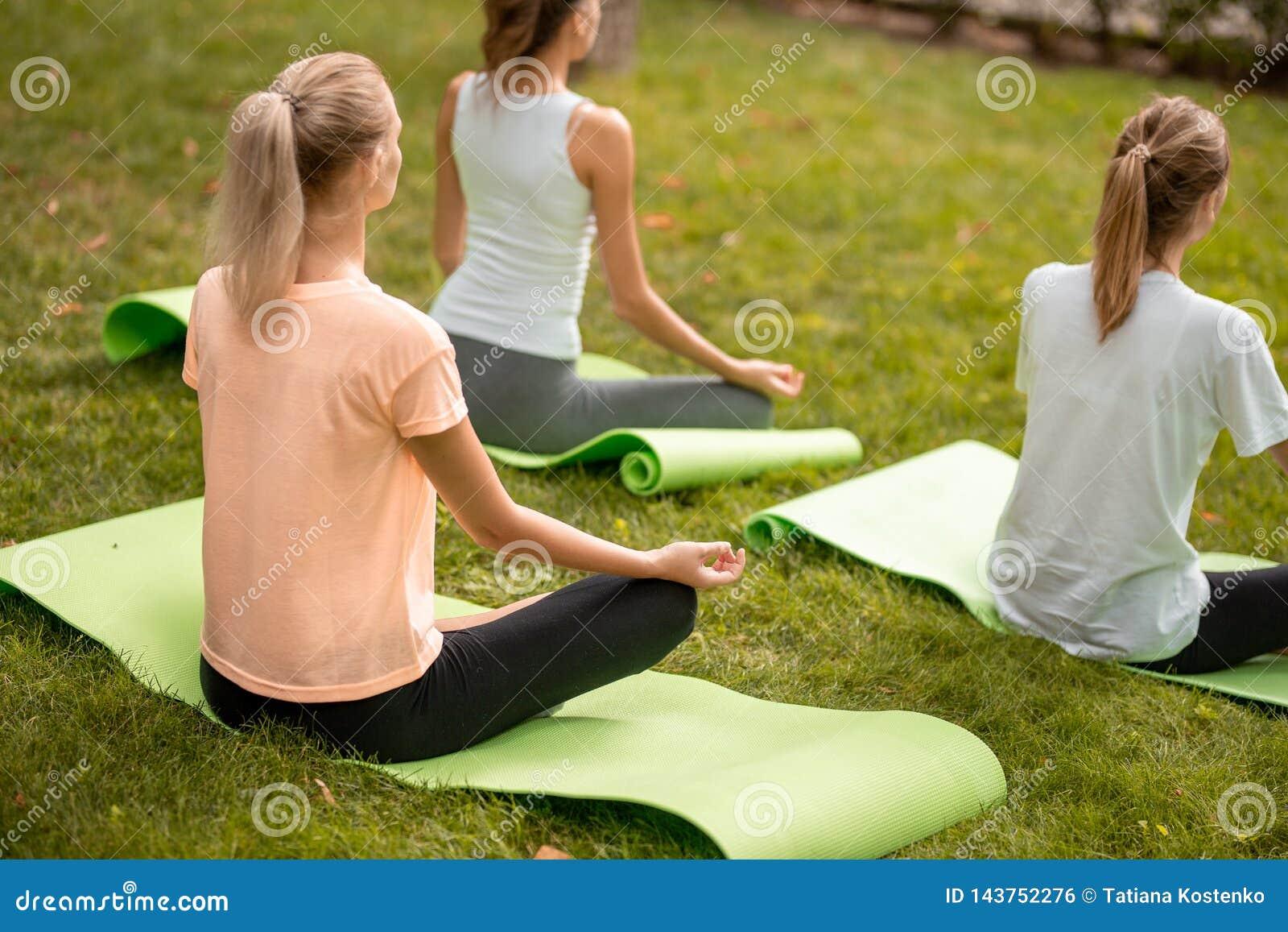Het jonge slanke meisje zit het ontspannen in de lotusbloempositie doend oefeningen op yogamatten met andere meisjes op groen gra