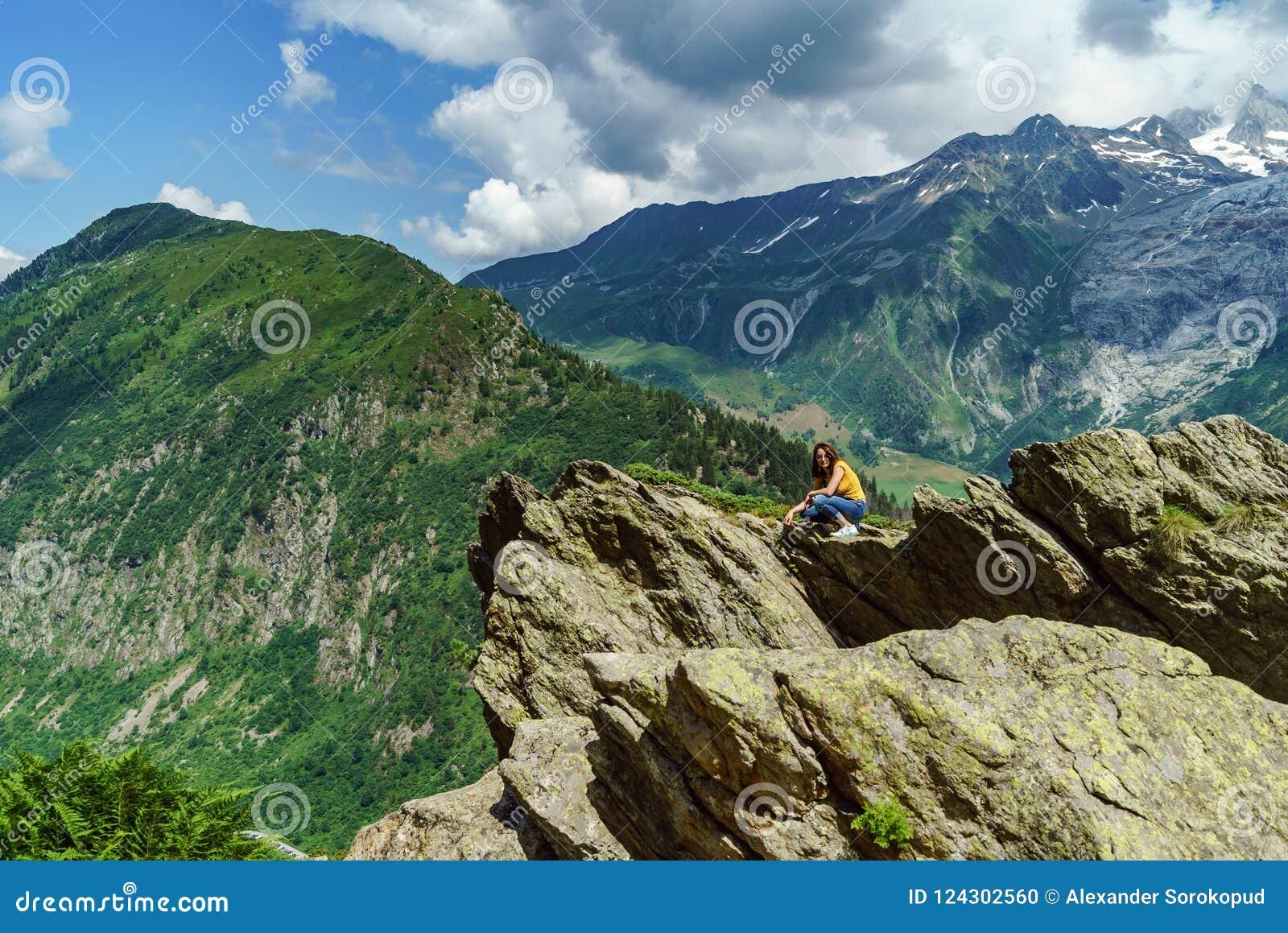 Het jonge tiener stellen op grote steen in Alpen