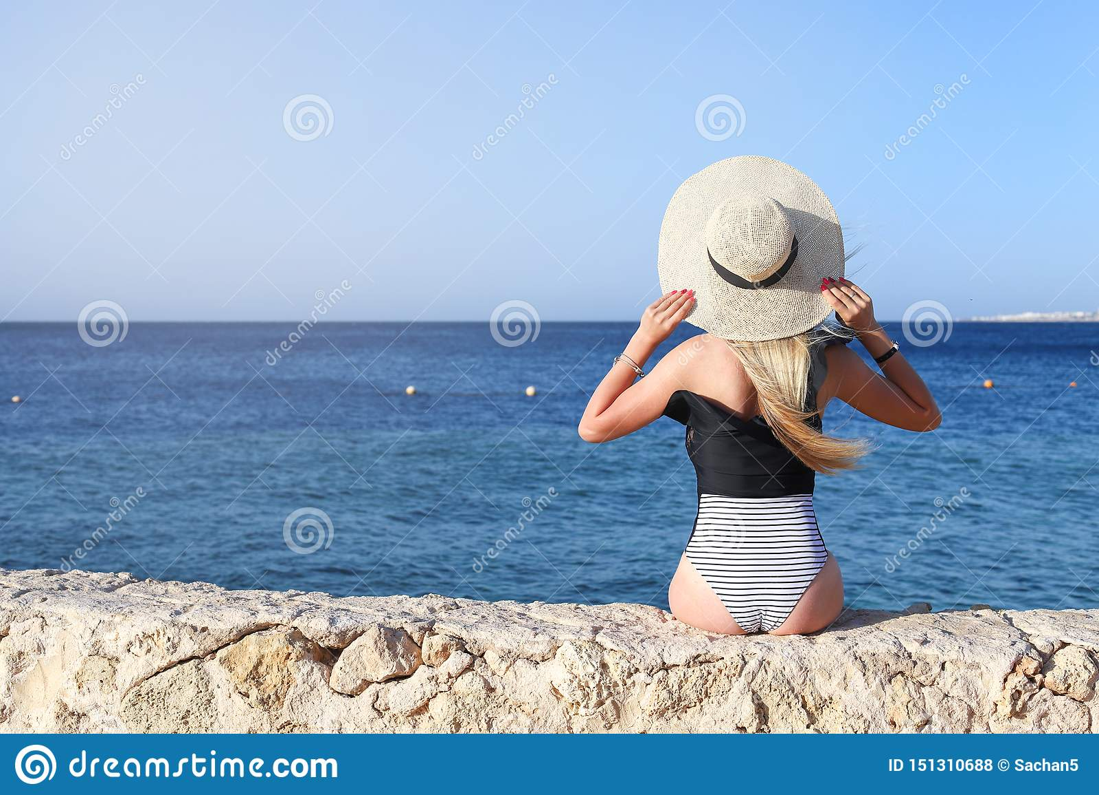 Het jonge vrij hete sexy vrouw ontspannen in zwempak op stenen met blauwe overzees en hemel op achtergrond De vakantieconcept van