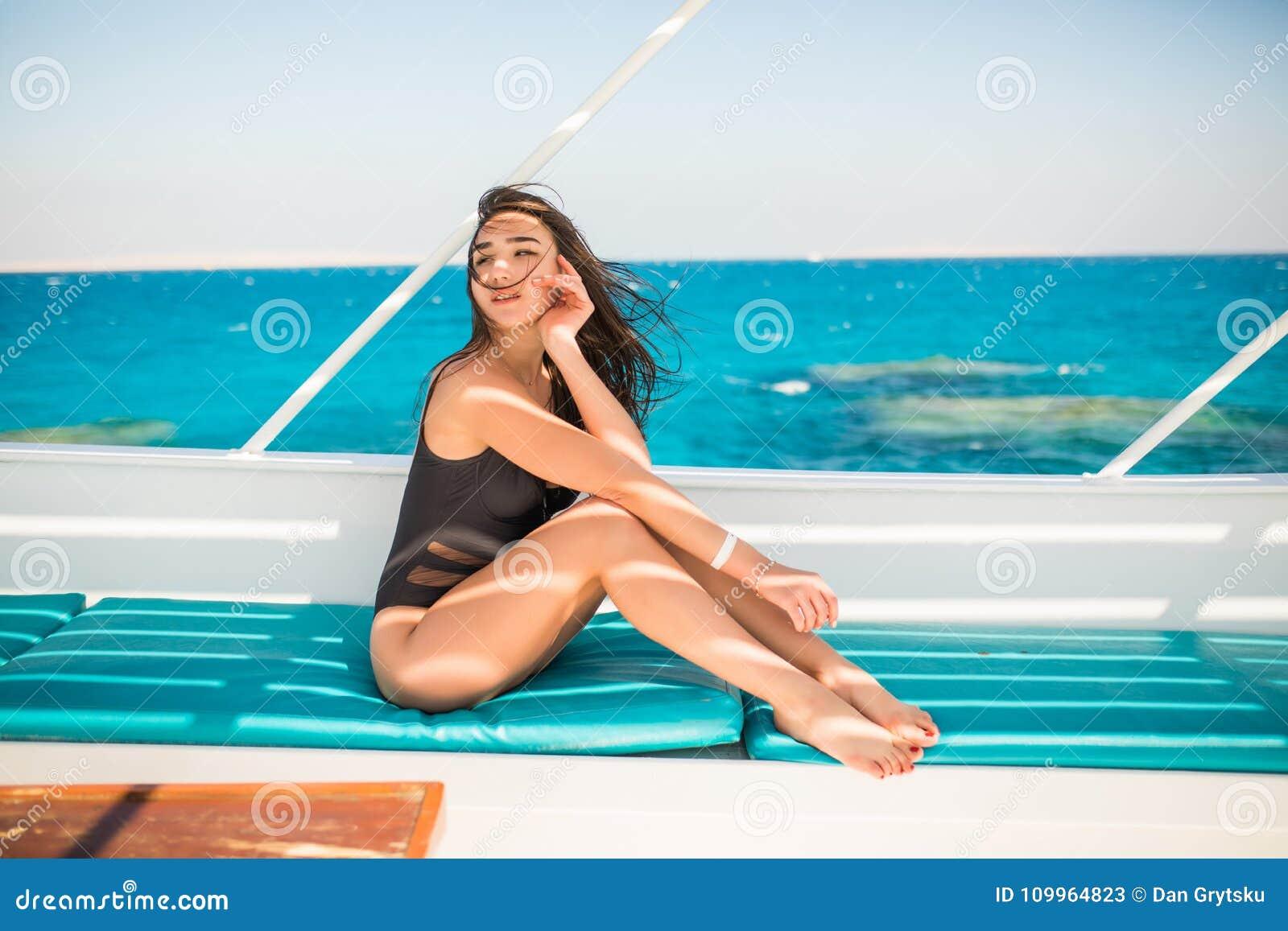 Het jonge Vrouw ontspannen aan boord van varend jacht in opean overzees
