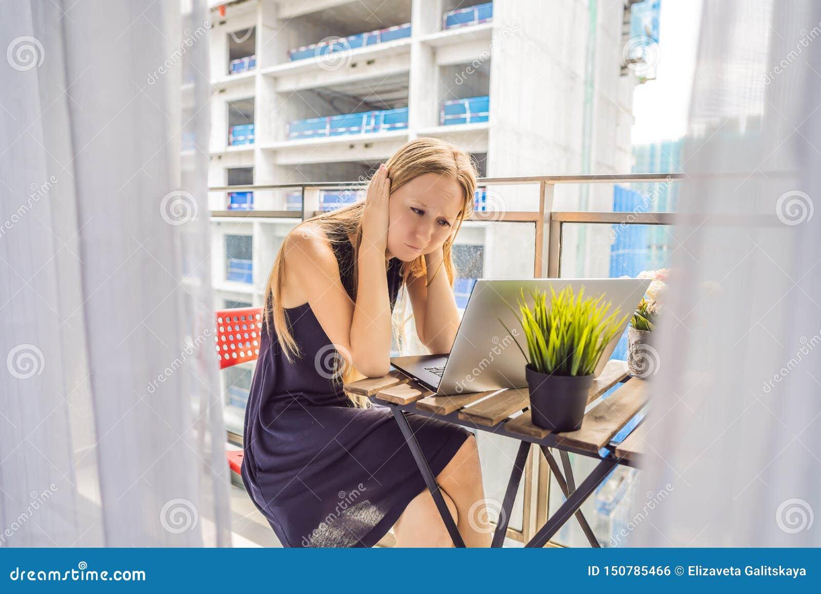 Het jonge vrouw proberen om aan het balkon te werken dat door te bouwen wordt geërgerd werkt buiten Lawaaiconcept Luchtvervuiling