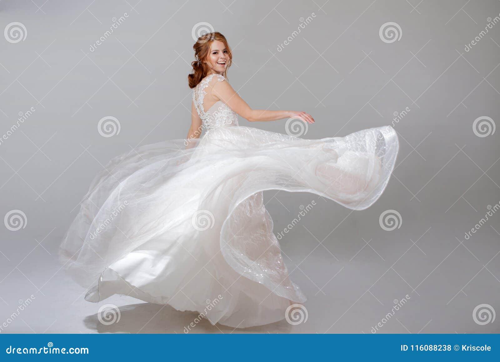 Het jonge vrouw spinnen in een curvy huwelijkskleding vrouwenbruid in overvloedige huwelijkskleding Lichte achtergrond