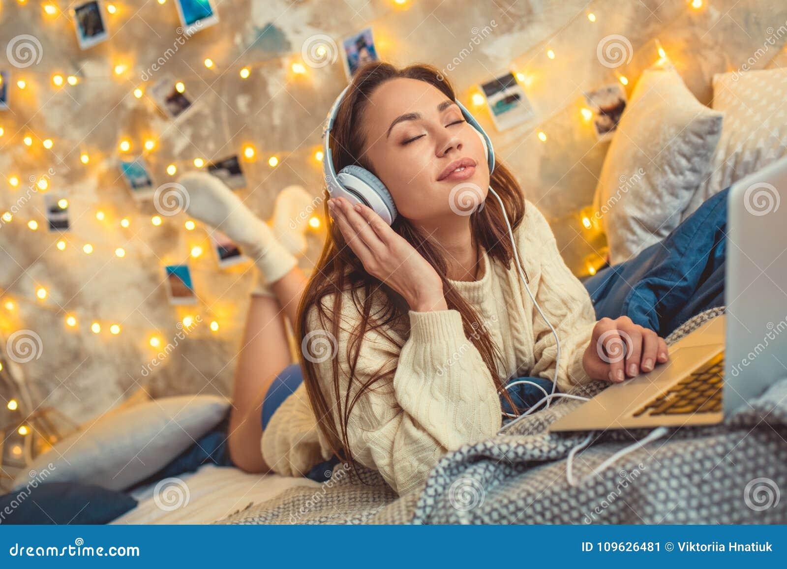 Het jonge vrouwenweekend verfraaide thuis slaapkamer luisterend aan favoriet lied