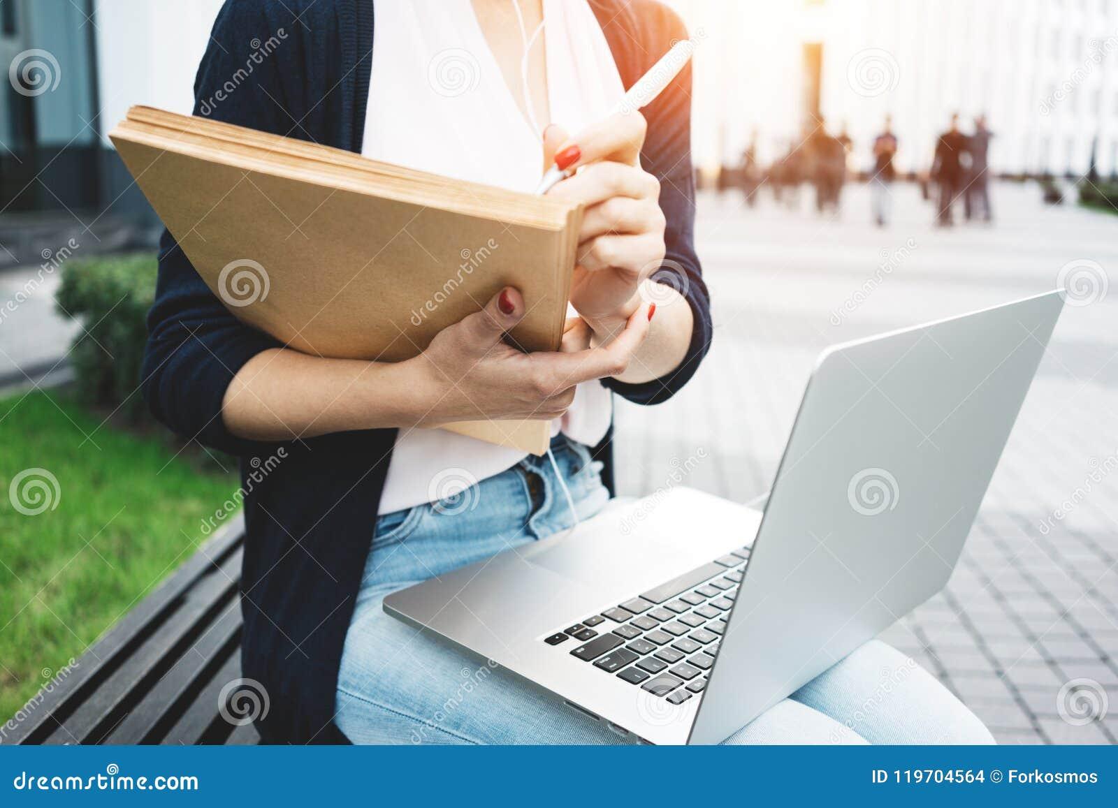 Het jonge wijfje die freelancer arbeidsmarktonderzoek naar moderne laptop maken, zit in openlucht in stedelijke straat