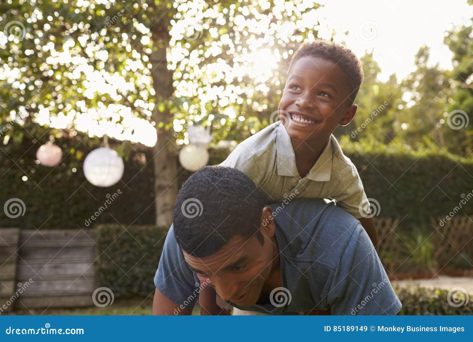 Het jonge zwarte jongen spelen op zijn dadï ¿ ½ s terug in een tuin