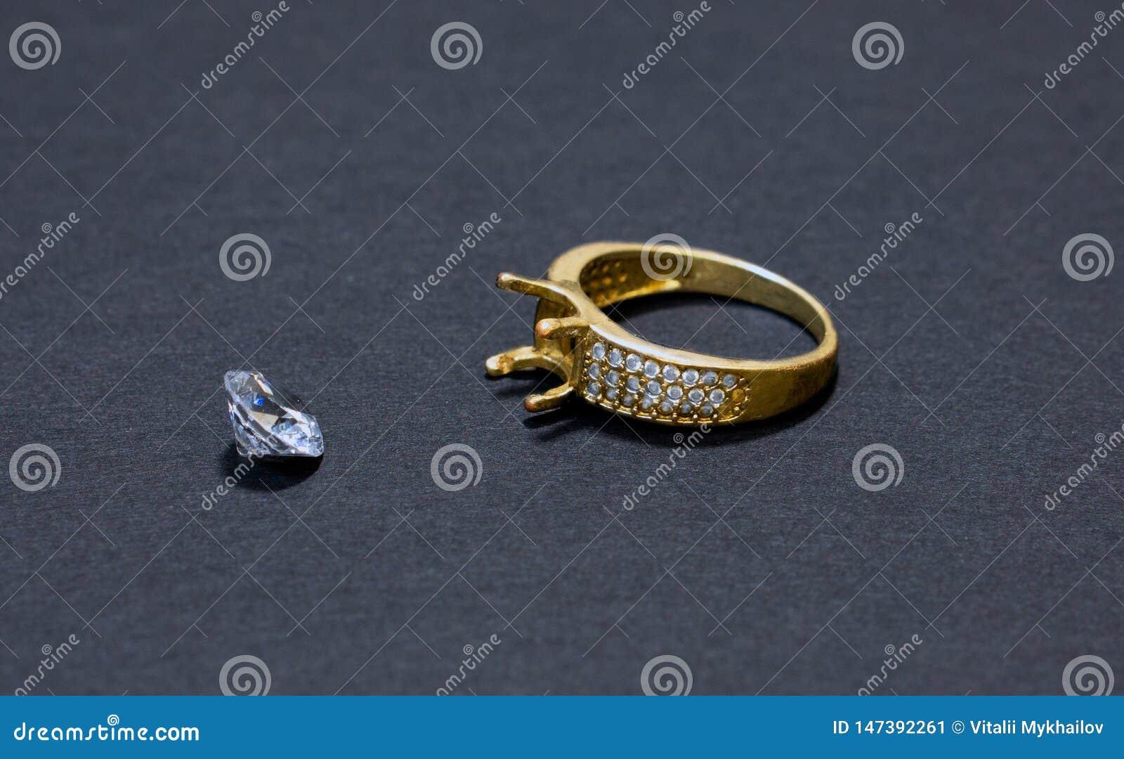 Het juwelenwerk, gouden ring met een diamant, voorbereiding voor het installeren van een steen op een ring, donkere achtergrond