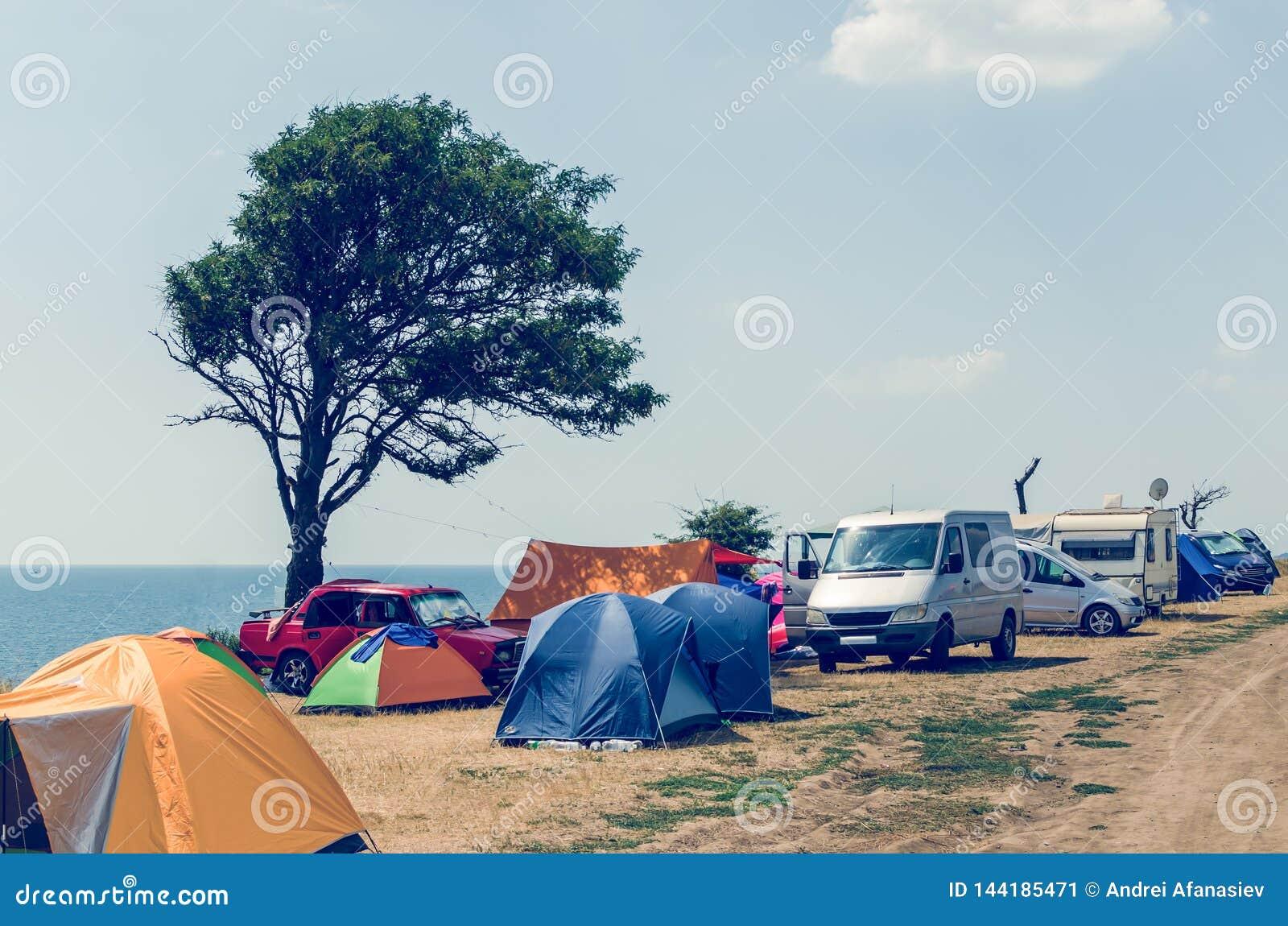 Het kamperen plaats dichtbij het overzees, de auto s en de tenten op het overzeese strand