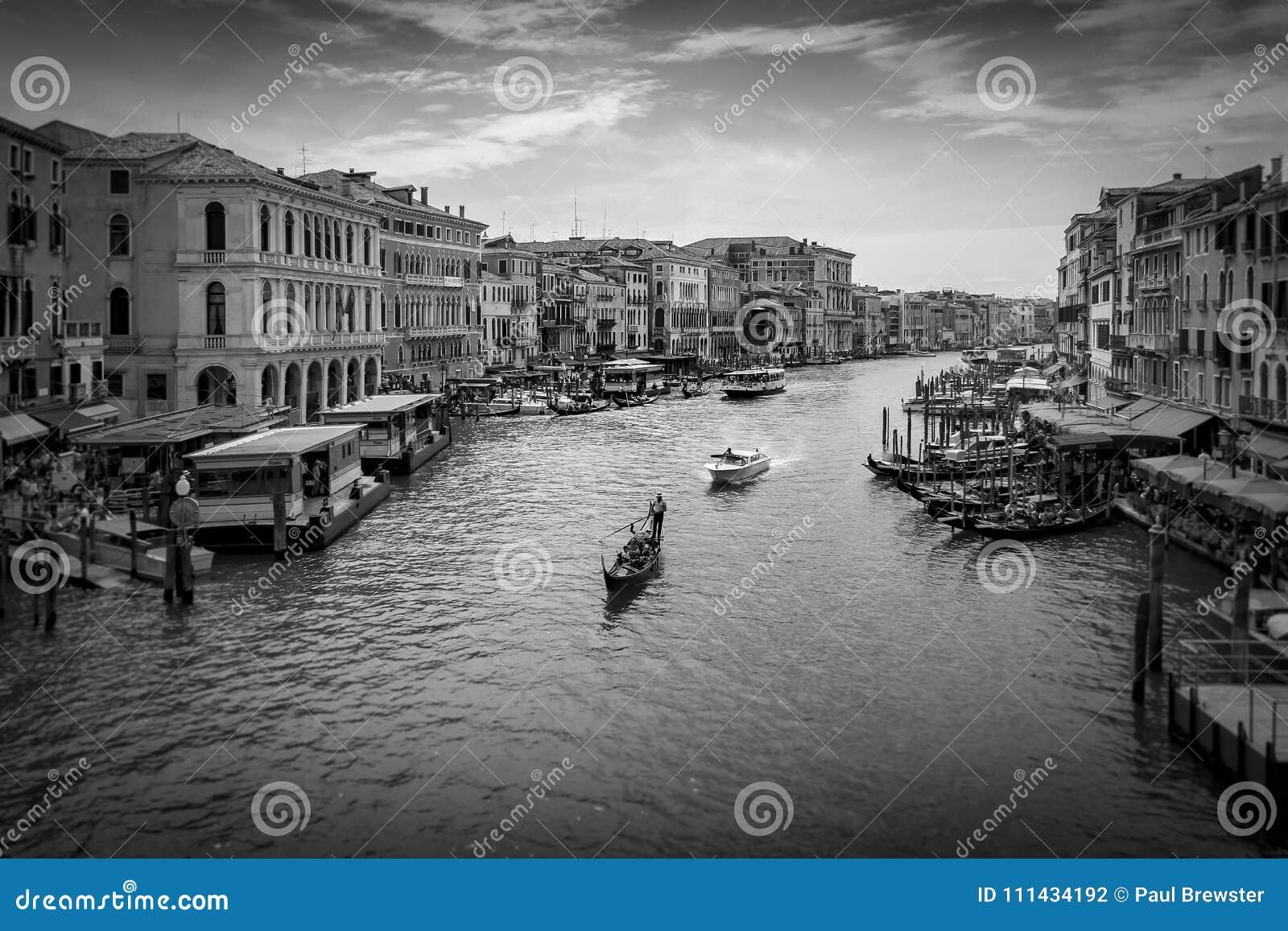 Het kanaal van Venetië en gondel en boten van de Rialto-Brug in zwart-wit