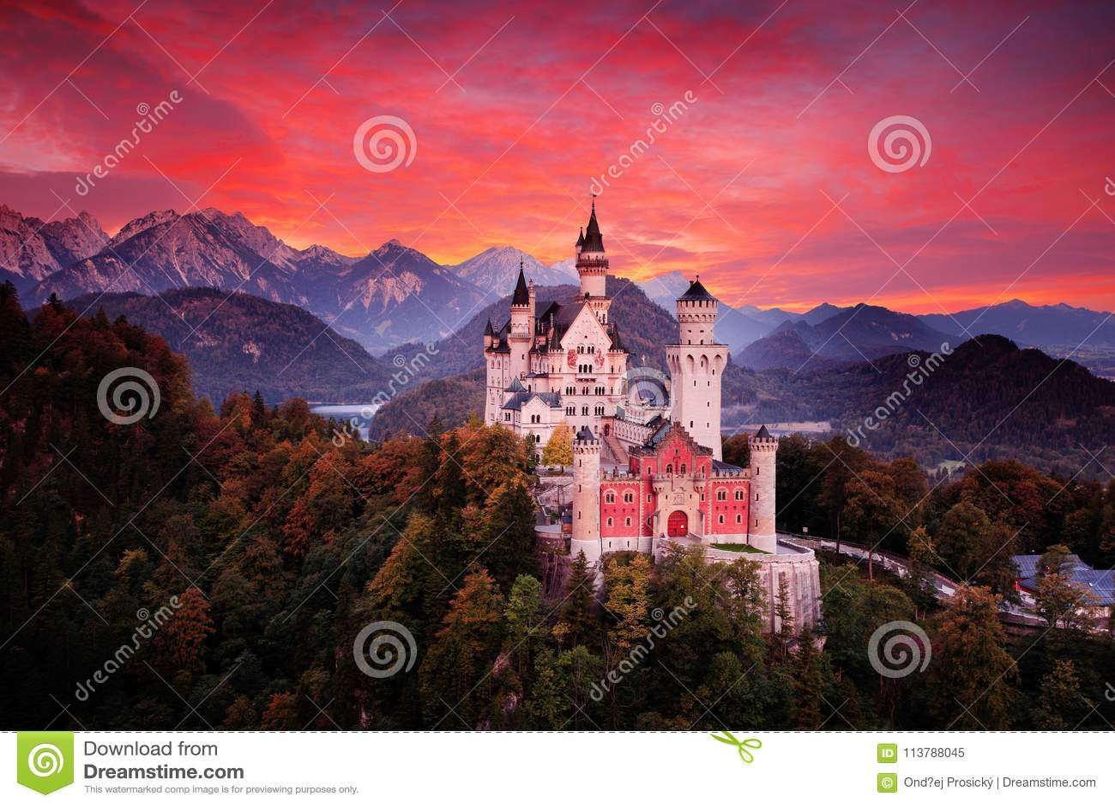 Het kasteel van het Neuschwansteinsprookje Mooie zonsondergangmening van de bloedige wolken met de herfstkleuren in bomen, scheme