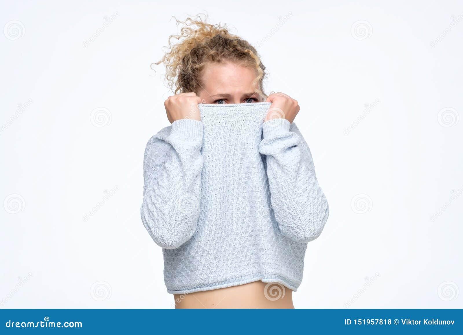 Het Kaukasische meisje met een sociale fobie verbergt haar gezicht in een sweater