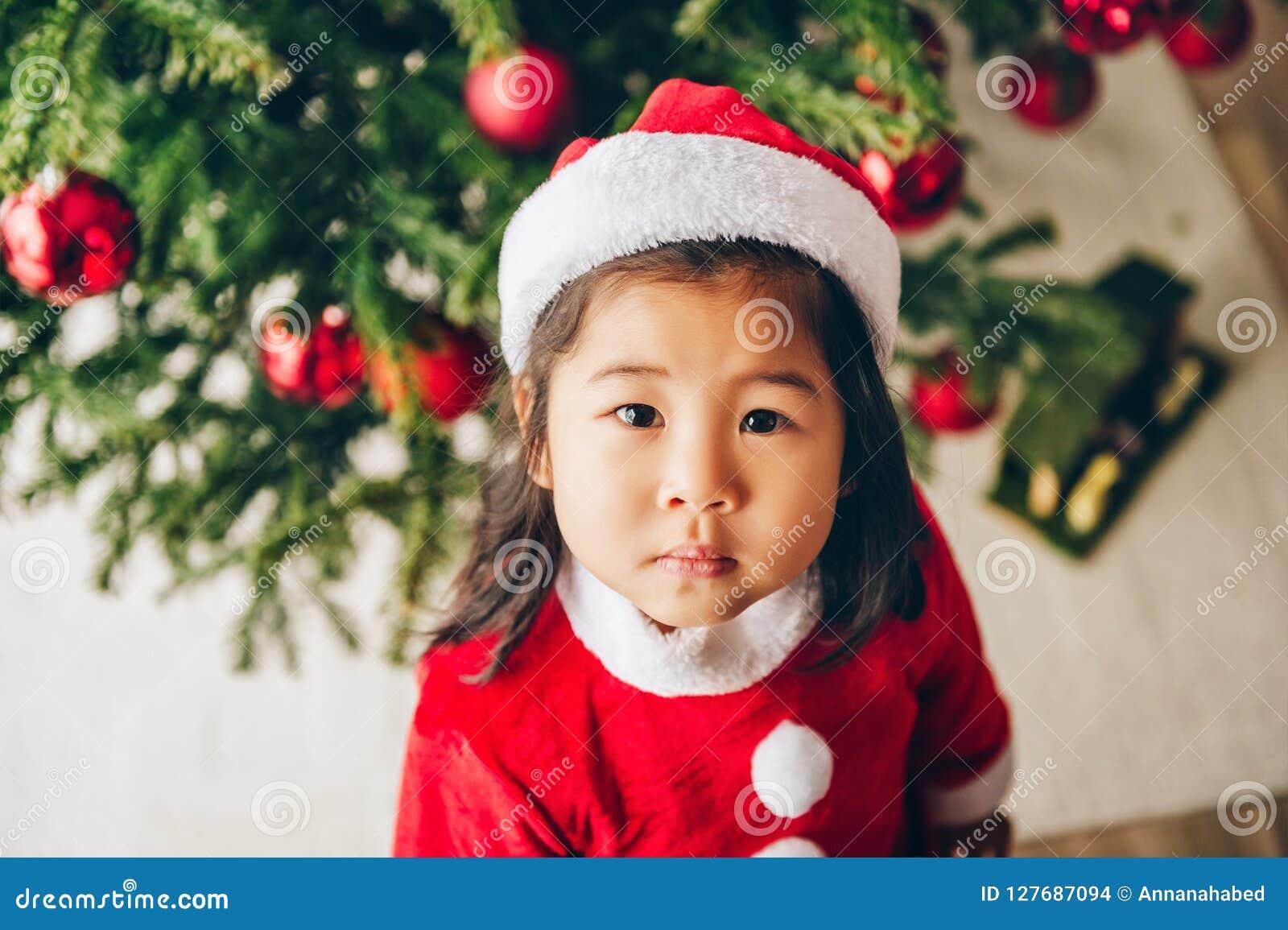 Het Kerstmisportret van het aanbiddelijke meisje die van de 3 éénjarigen Aziatische peuter rode Kerstman dragen kleedt zich en ho
