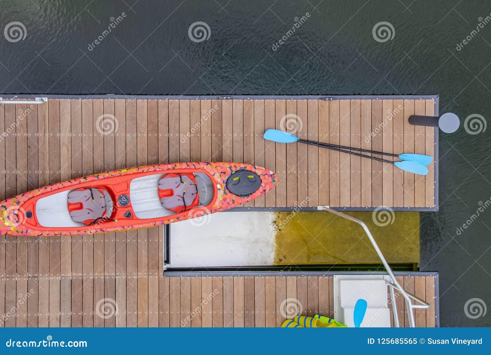 Het kijken neer op een dok in het water met een kayack en peddels en reddingsvesten naast een kayac lanching platform