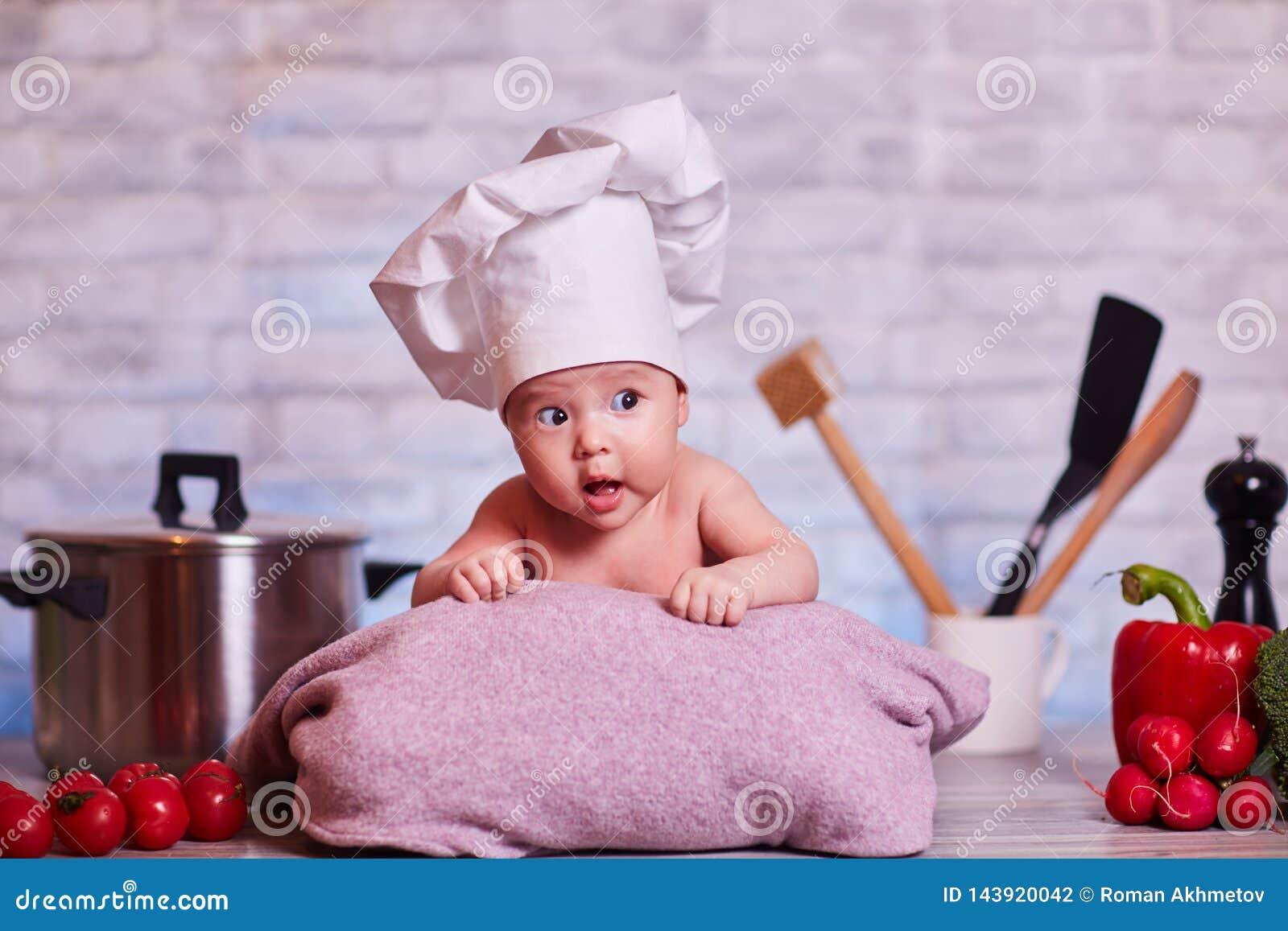 Het kind, babymeisje ligt op de keukenlijst in GLB van een chef-kok - naast hem zijn groenten, groene paprika, radijs, juiste bro