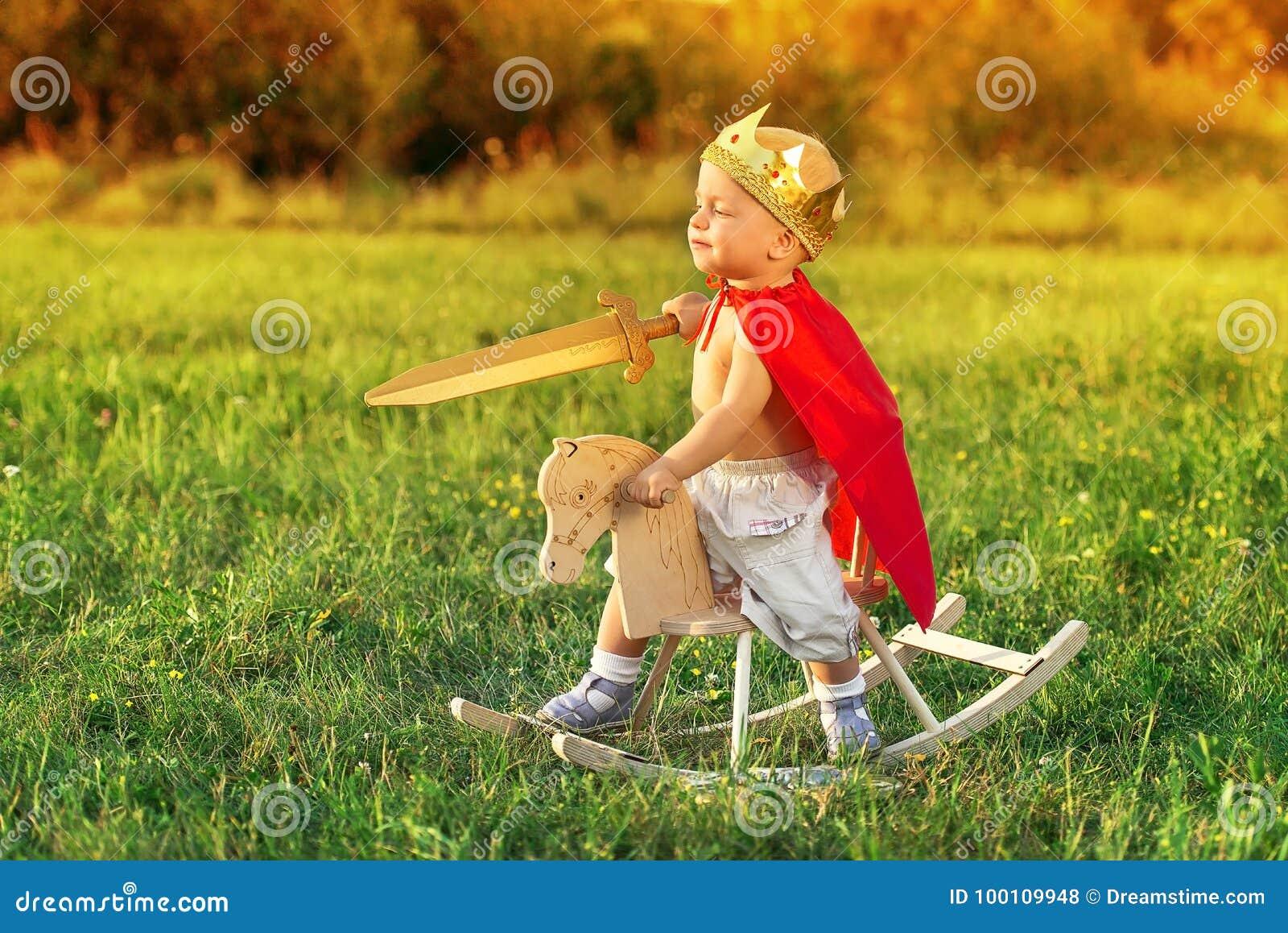 e22bbd2d7b9 De koning het kind schrijlings op een paard speelt met een zwaard Weinig  Prins met een kroon op het hoofd en in een rode regenjas