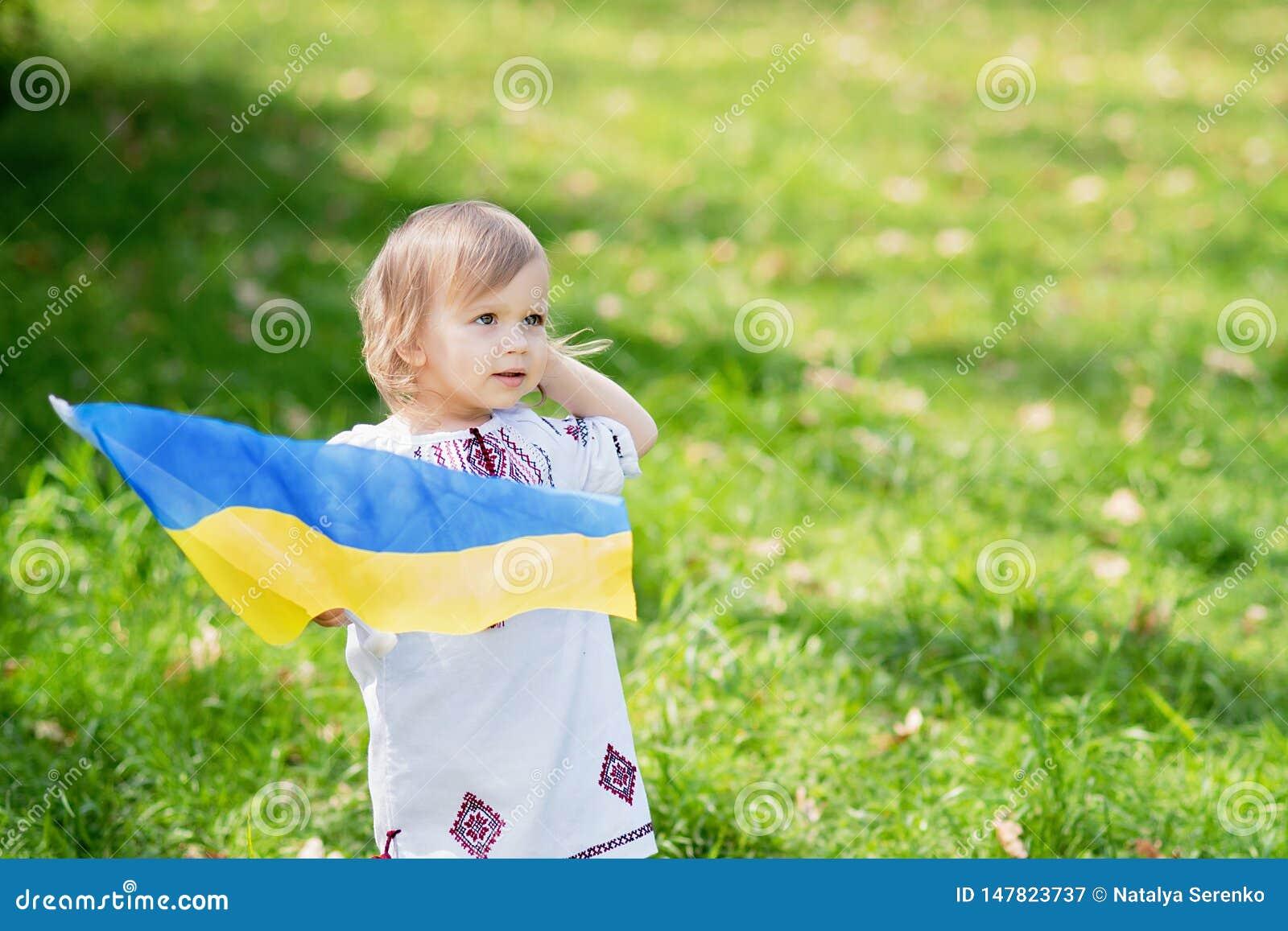Het kind draagt fladderende blauwe en gele vlag van de Oekra?ne op gebied De Onafhankelijkheidsdag van de Oekra?ne ` s De Dag van