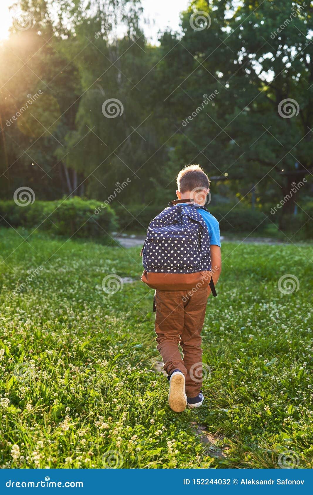 Het kind gaat naar school de jongensschooljongen gaat naar school in de ochtend gelukkig kind met een binnen aktentas op zijn rug