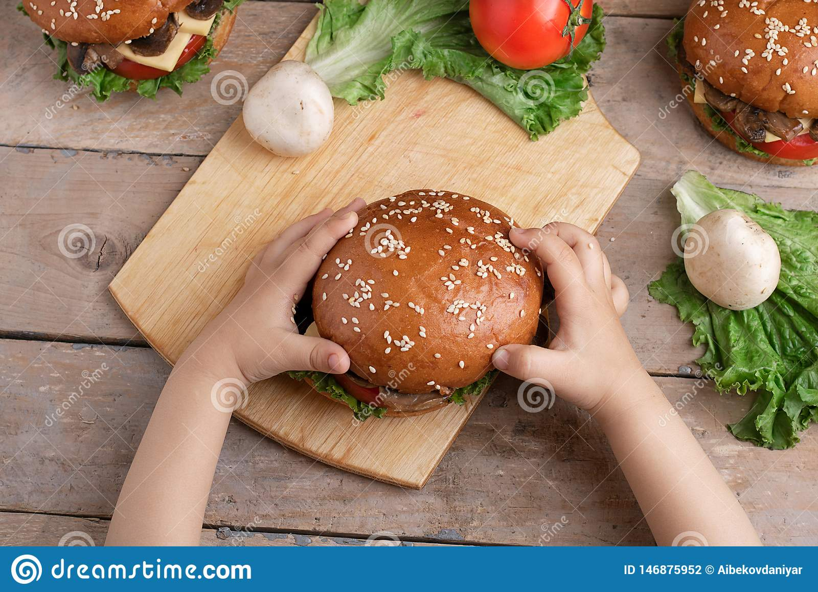 Het kind houdt rond paddestoelhamburger, rauwe groenten
