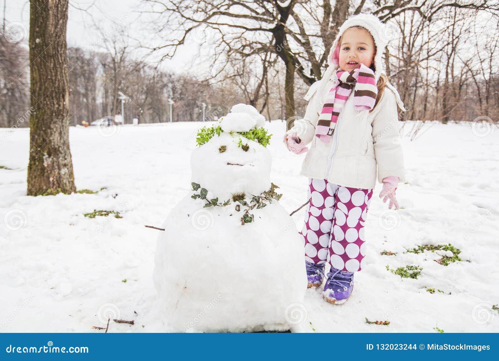 Het kind maakt een Sneeuwman in het Park bij de Winterdag