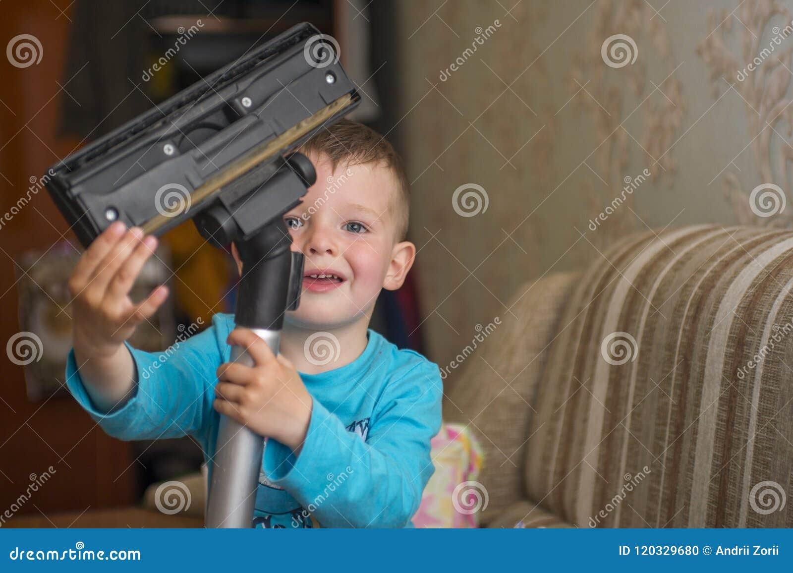 Het kind maakt het huis met een stofzuiger schoon