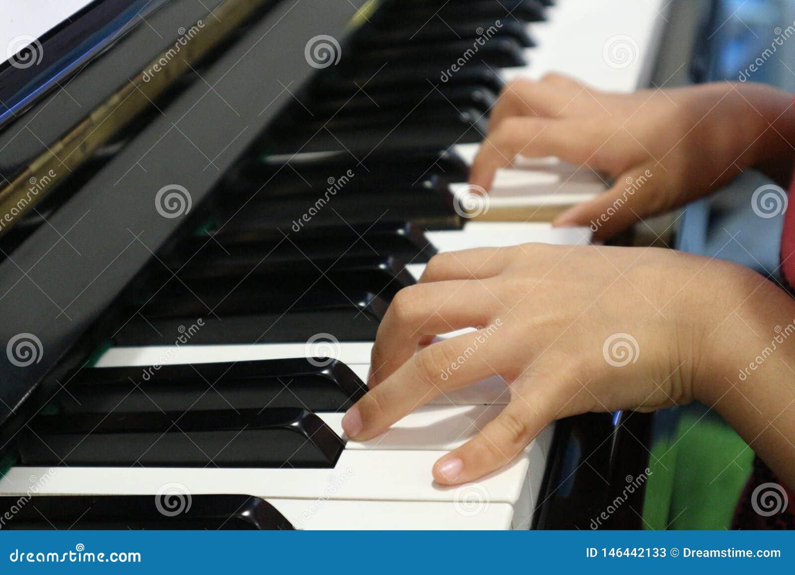 Het kind overhandigt het spelen piano