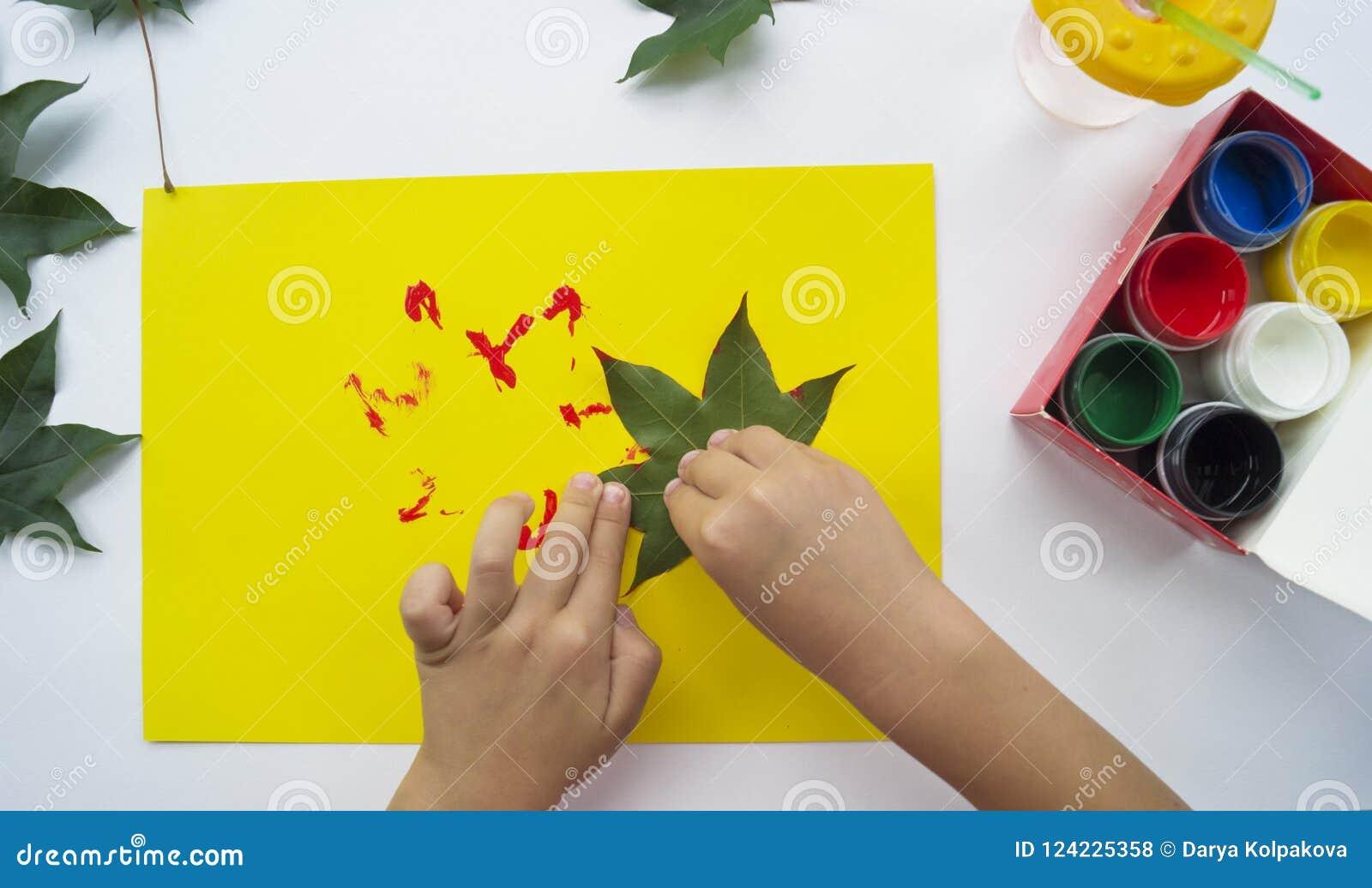 Het kind schildert een beeld van de herfstblad met verven