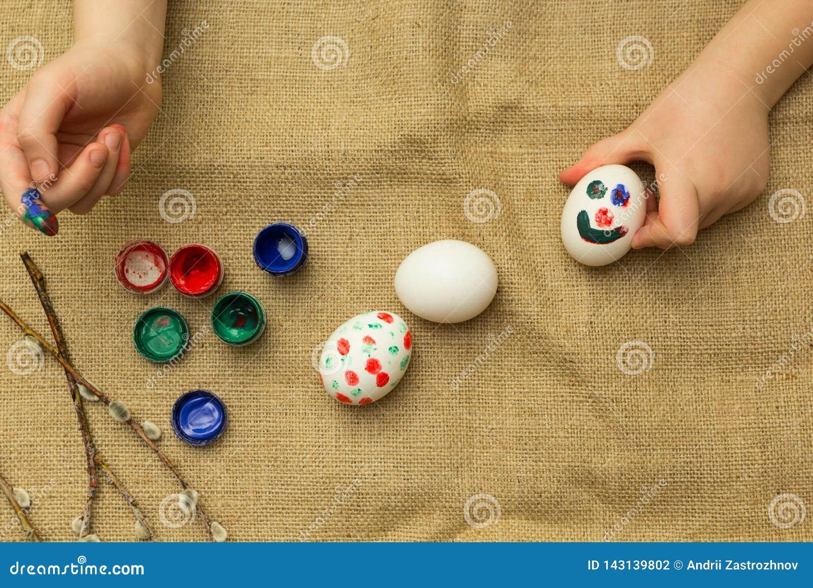 Het kind schildert eieren voor Pasen