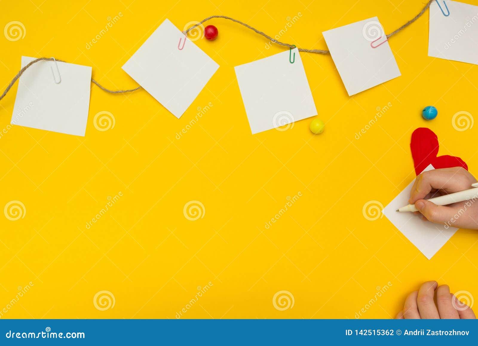 Het kind schrijft een nota over een blad van document op de drooglijn Heldere achtergrond