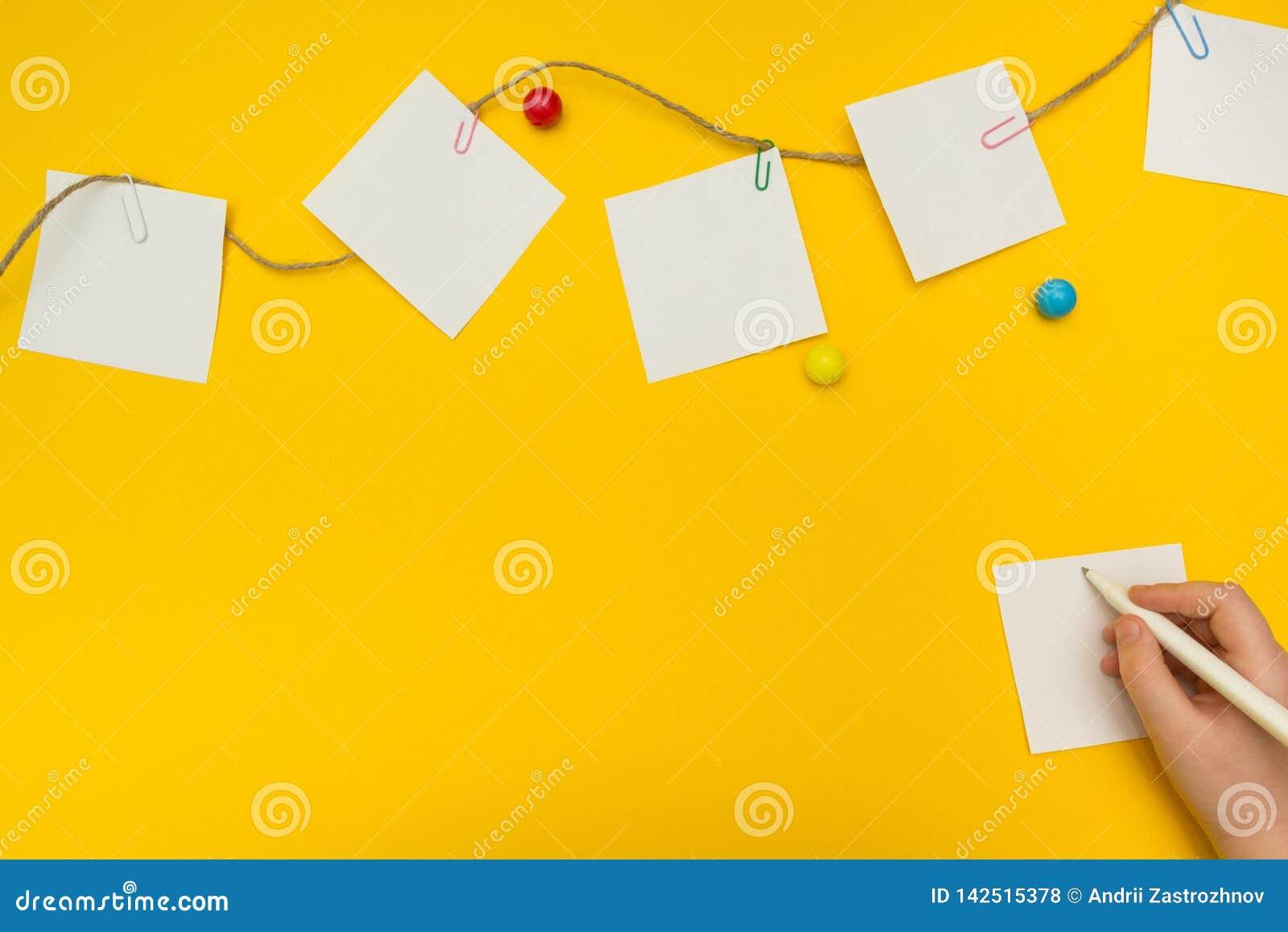 Het kind schrijft een nota over een gele achtergrond De document nota s