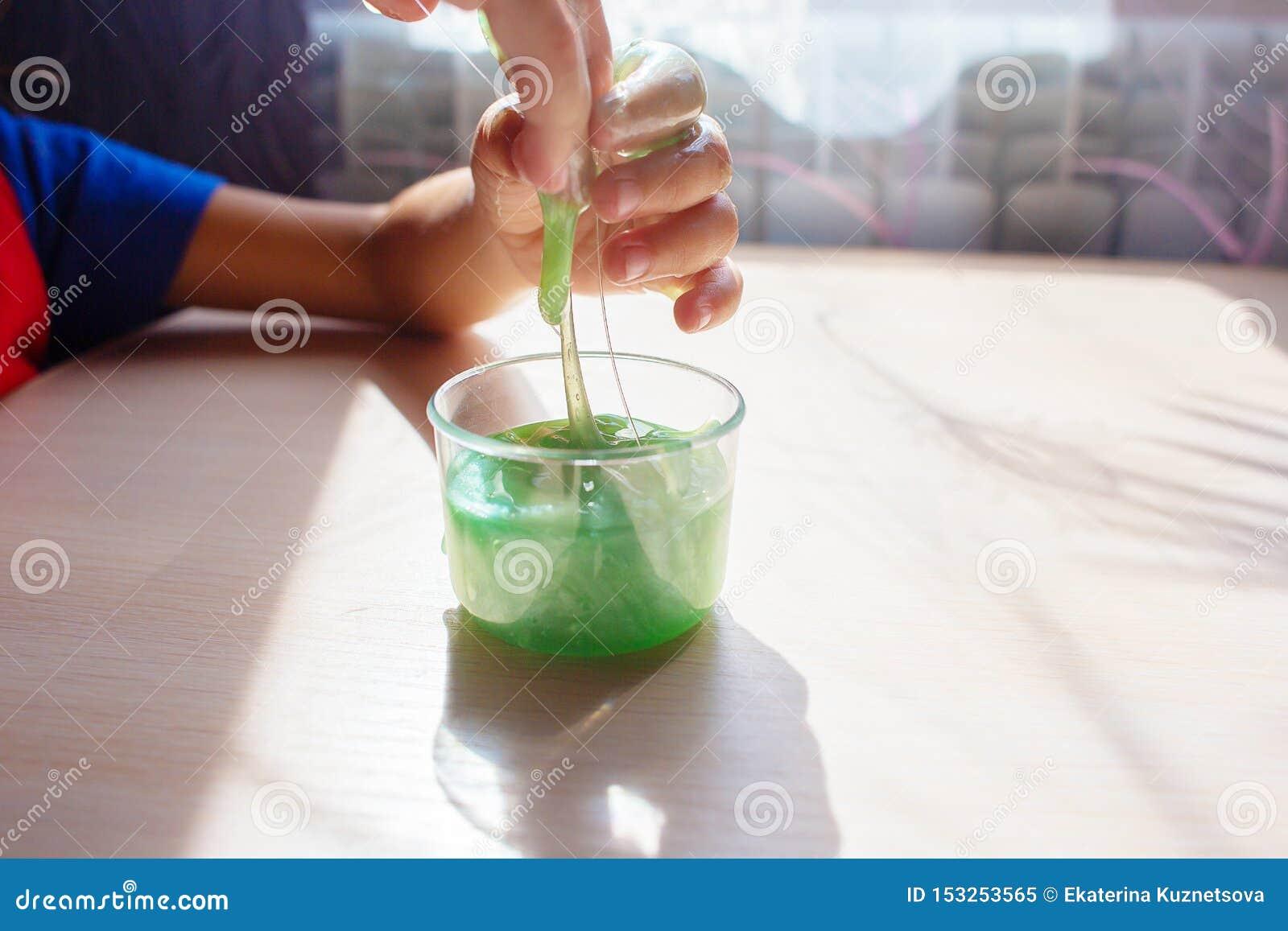 Het kind speelt met toffee een slijm van groene kleur De handen sluiten omhoog