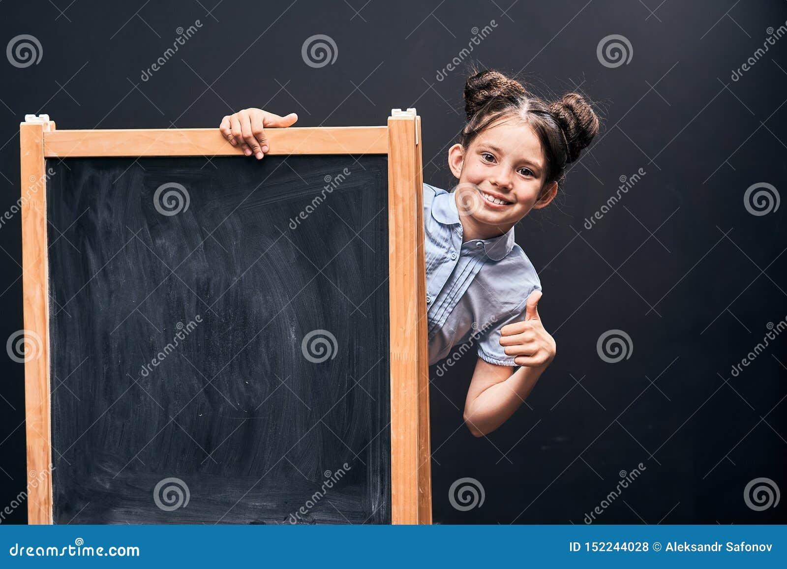 Het kind toont een teken van goedkeuring die zich bij de schoolraad bevinden positief schoolmeisje die uit van achter een zwarte
