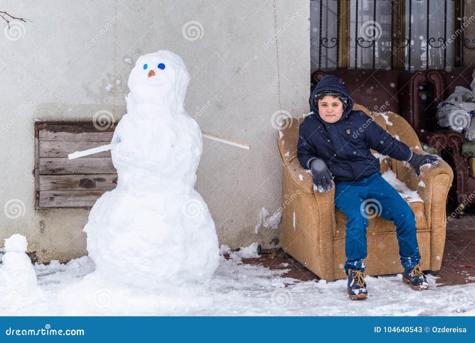 Het kind zit op een laag nadat hij sneeuwman beëindigde