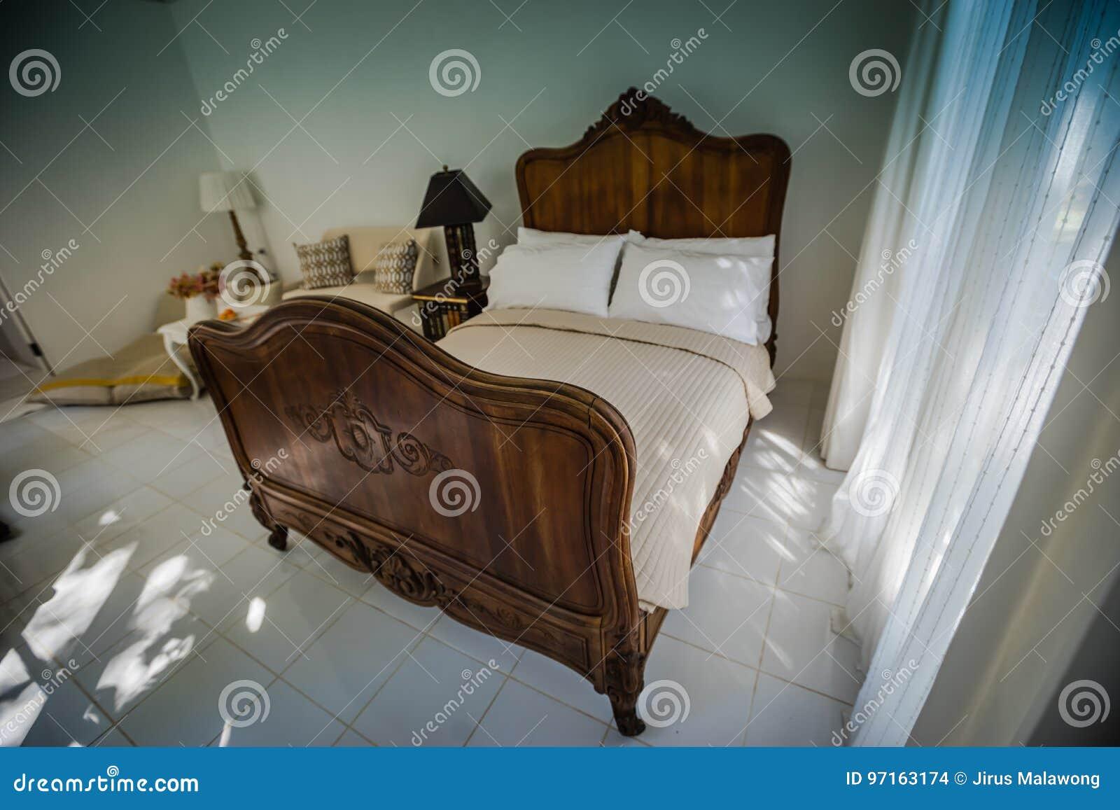 het klassieke meubilair van het teak houten bed in de warme en comfortabele slaapkamer ne