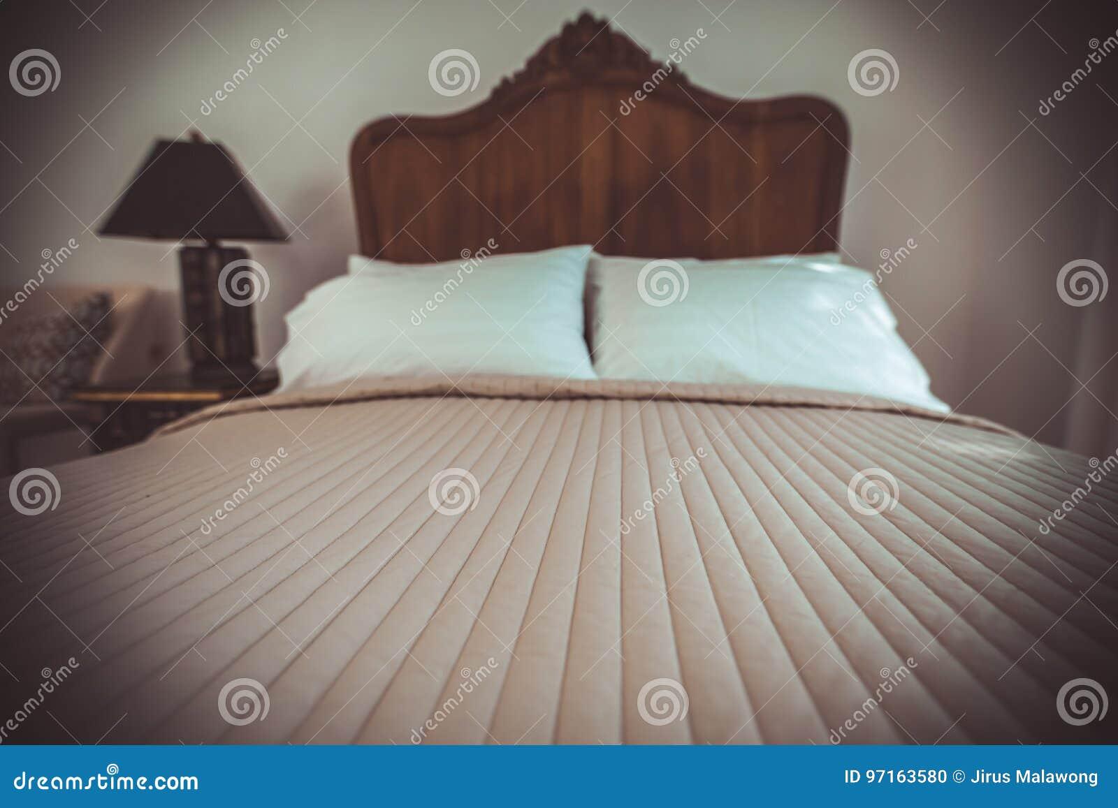 het klassieke meubilair van het teak houten bed in de warme en comfortabele slaapkamer naast de vensters met ochtendzonlicht