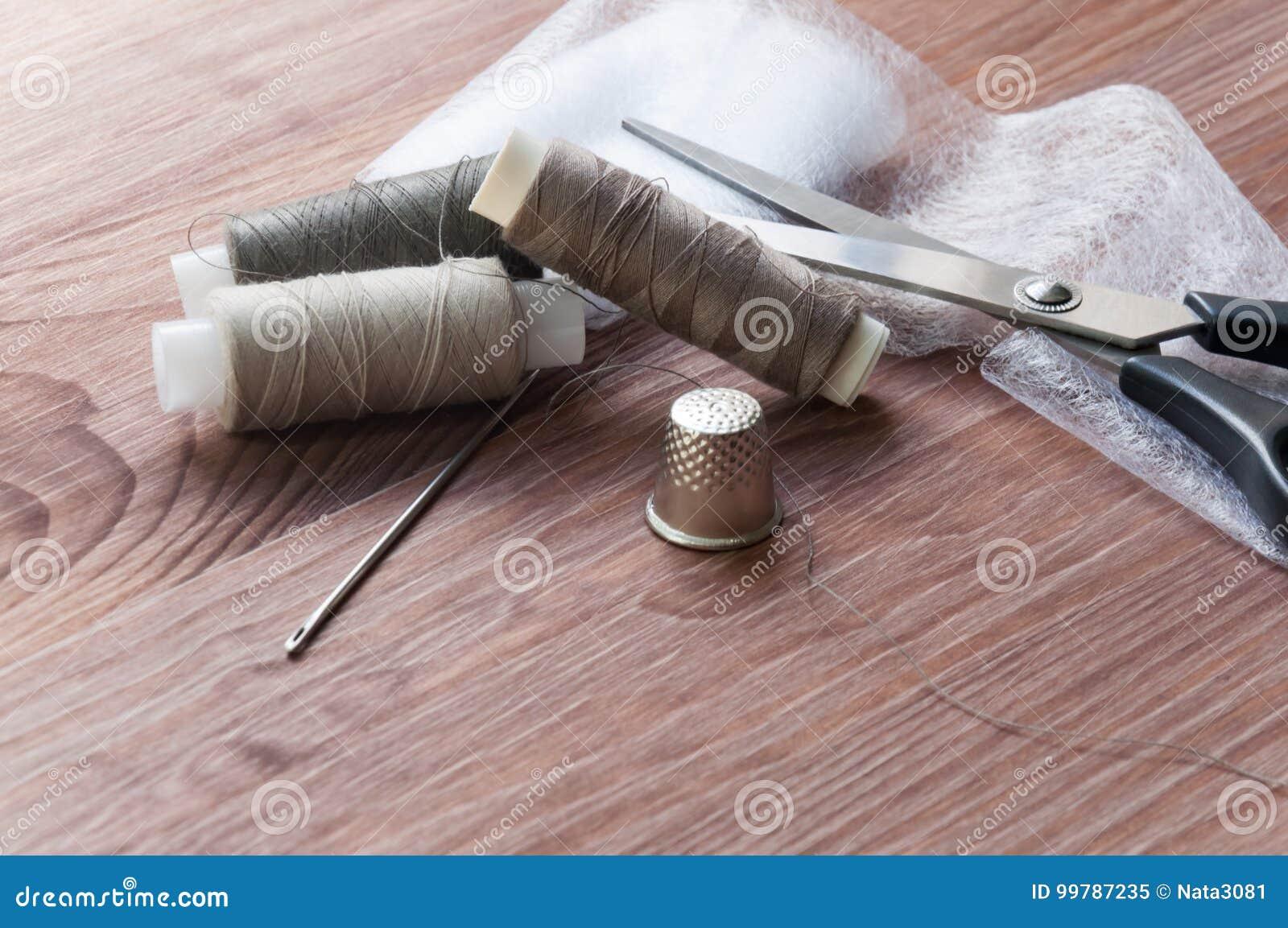 Het kleermakers` s bureau Oude naaiende houten trommels of strengen op oude houten worktable met schaar