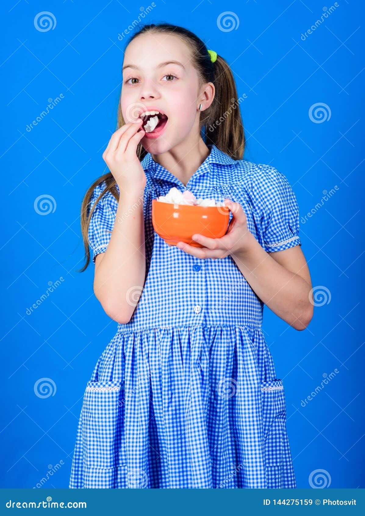 Het kleine meisje eet heemst Het op dieet zijn en calorie Zoet tandconcept de gelukkige snoepjes en de traktaties van weinig kind