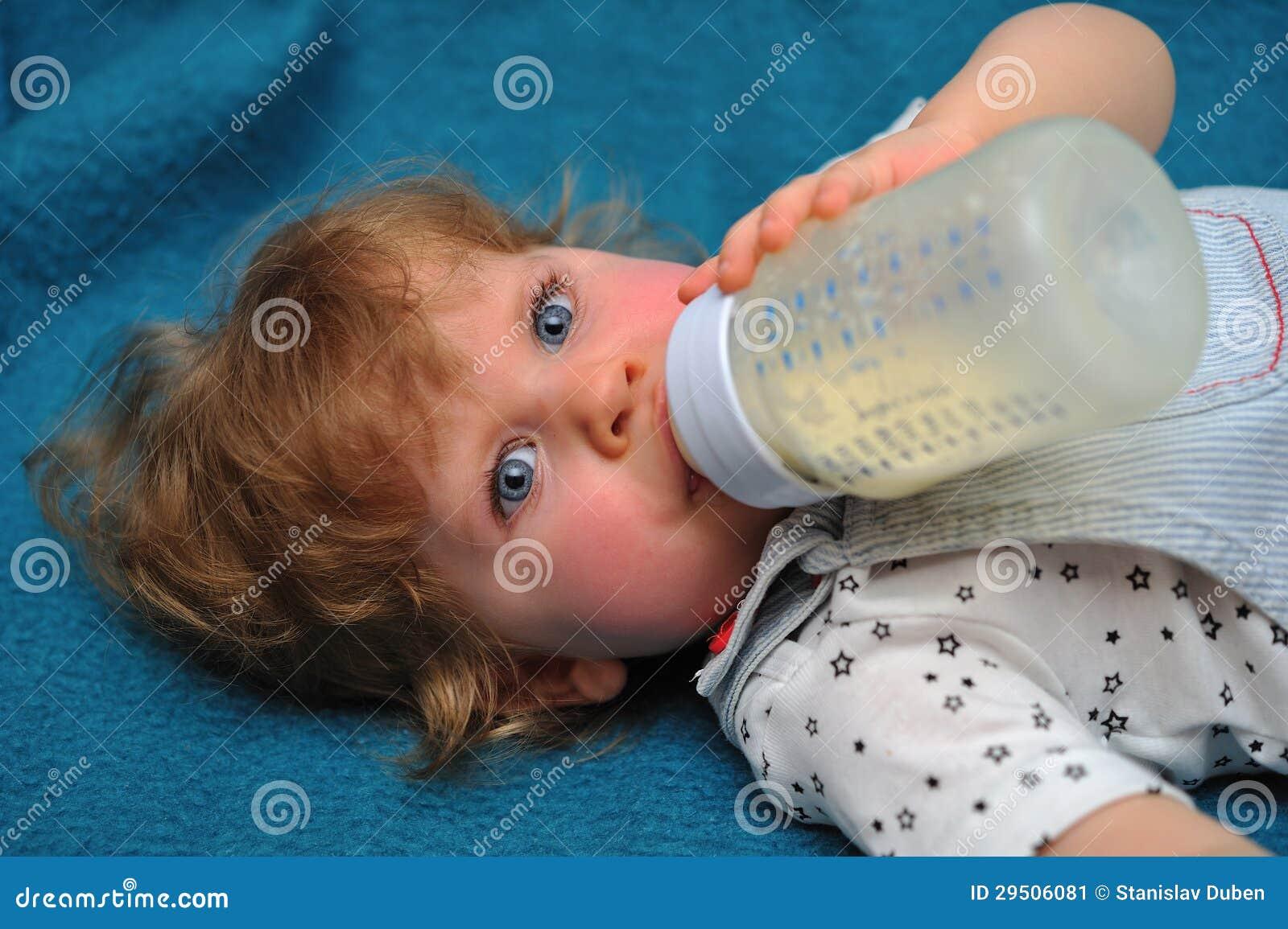 Het kleine meisje liggen op blauwe bank en drinkt melk van fles