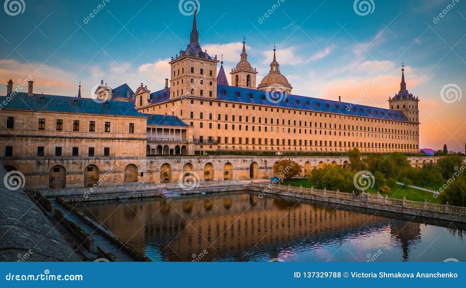 Het klooster en de koninklijke plaats Gr Escorial in Spanje bij zonsondergang met bezinning in een vijver