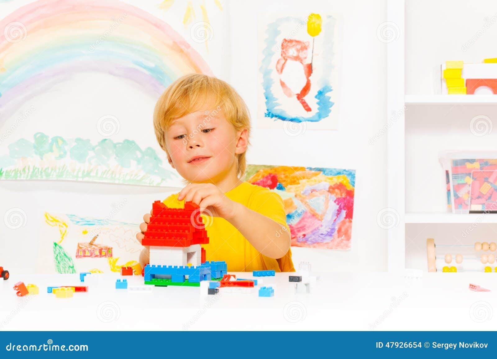 Het knappe blonde jongen spelen met plastic blokken