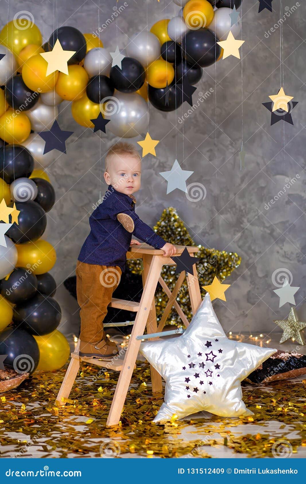 Het knappe jongen stellen op partijdecoratie met reusachtige grote gouden ster Grijze achtergrond zilveren sterren en verschillen