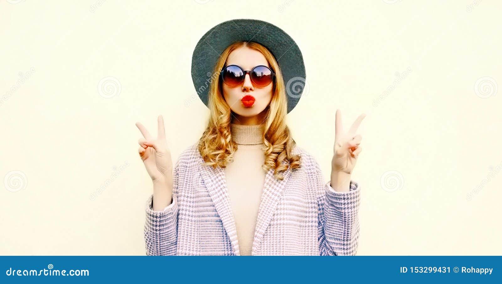 Het koele meisje die van het portretclose-up rode lippen blazen die luchtkus in ronde hoed verzenden