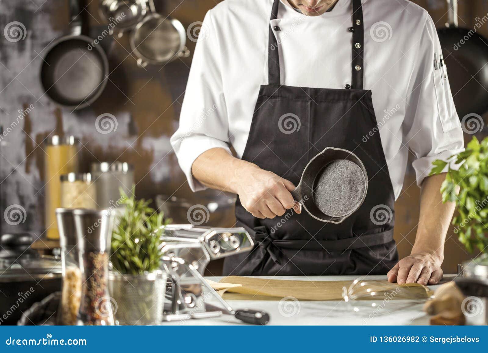 Het koken, beroep en mensenconcept - mannelijke chef-kokkok die voedsel maken bij restaurantkeuken