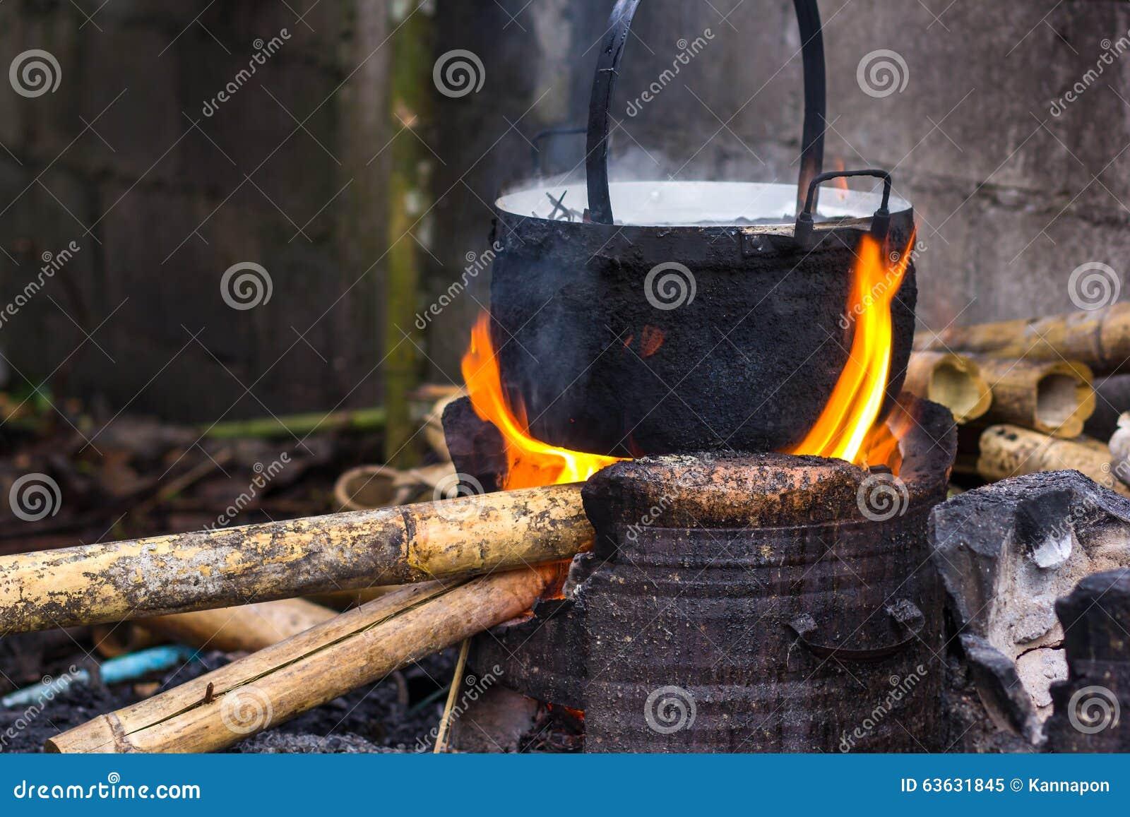 Het koken in ketel door vlammen op open brandfi dat wordt gelikt