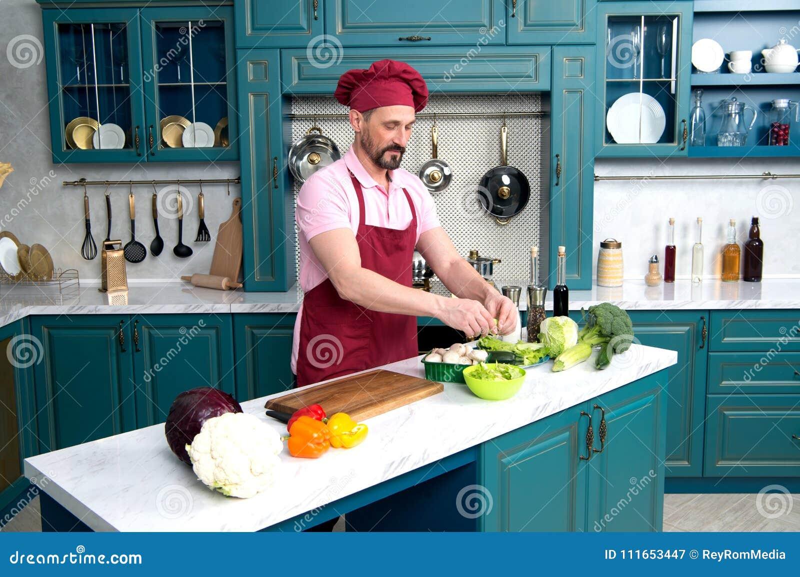 Het koken van de chef-kok bij keuken De mens op keuken die verse vegetarische ontbijtkerel koken bereidt salade met groene groent