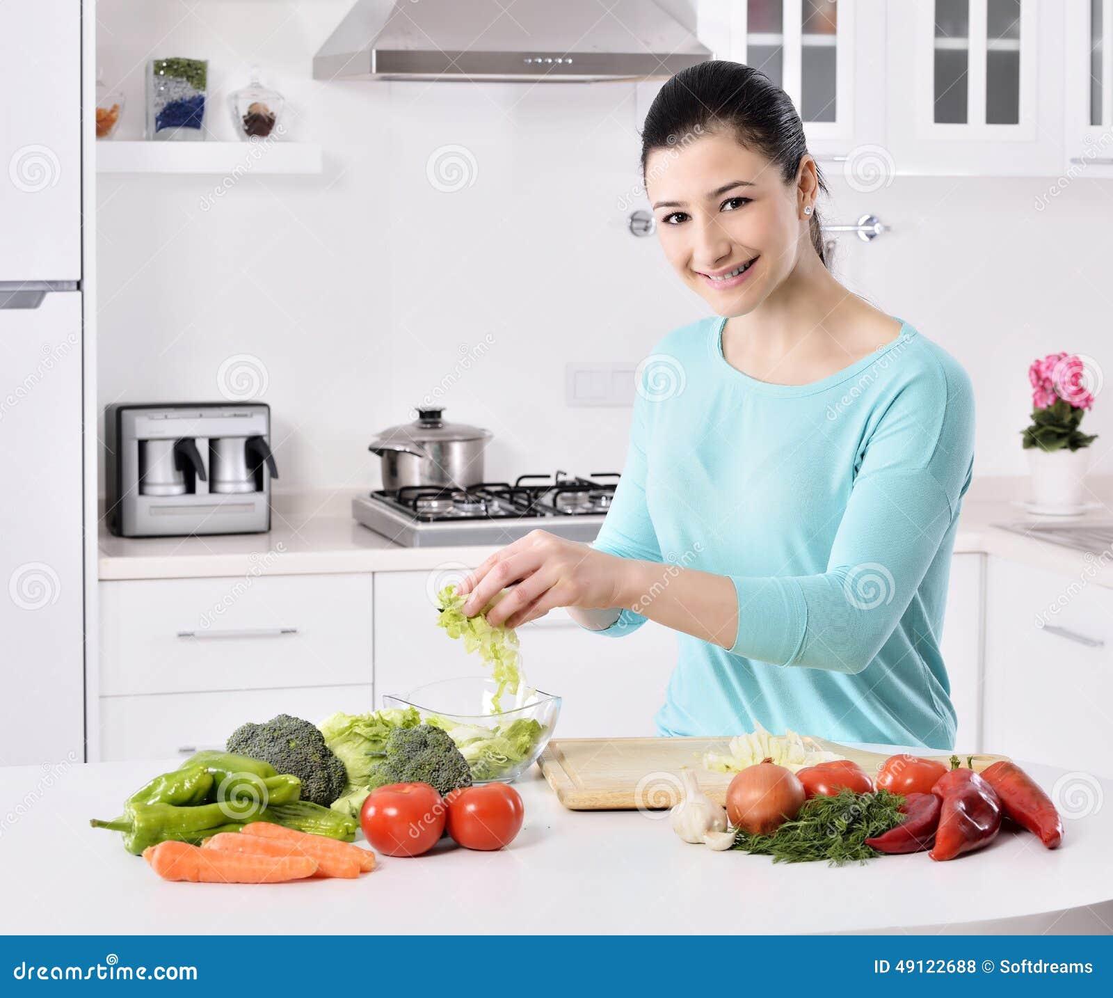 Het koken van de vrouw in nieuwe keuken die gezond voedsel met groenten maakt