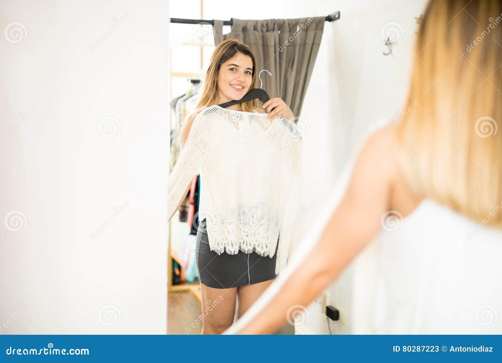 fa110966040026 De leuke vrouw die zich in een spiegel bekijken terwijl het proberen van  sommige nieuwe kleren bij een kleding slaat op