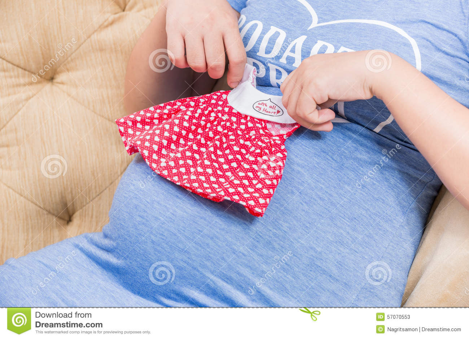 Het kostuum van de jonge zwangere baby van het vrouwenspel in handen met haar meisje