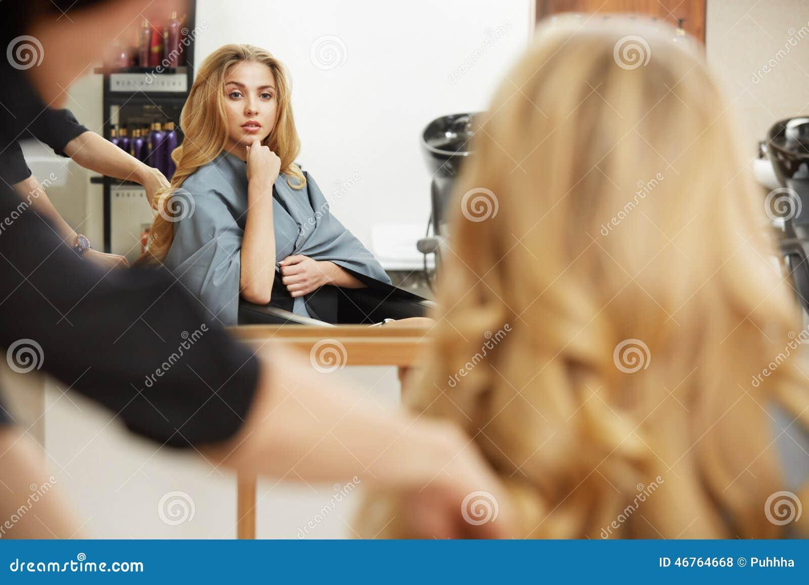 Het krullende haar van de blonde Kapper die kapsel voor jonge vrouw i doen