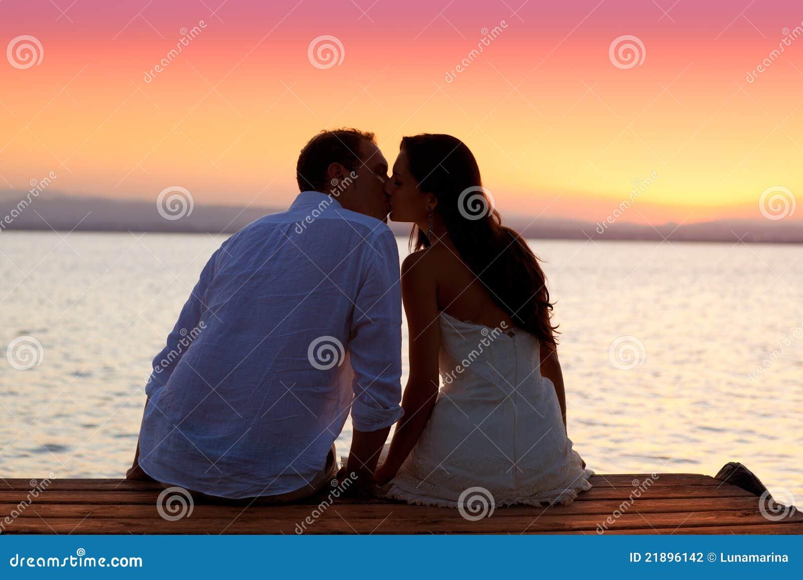 Het kussen van het paar bij zonsondergangzitting in pier