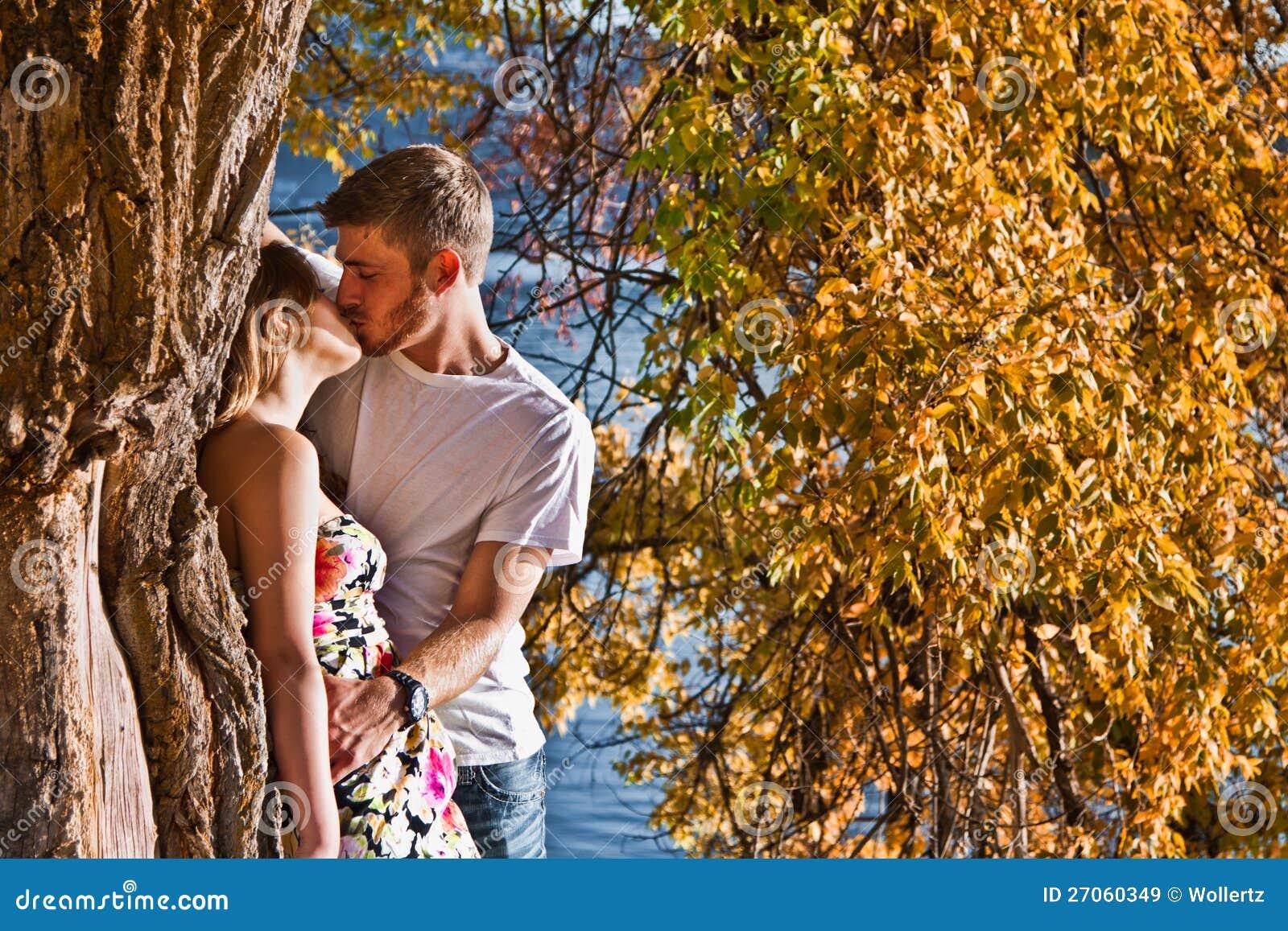 Het kussen van het paar in de herfst
